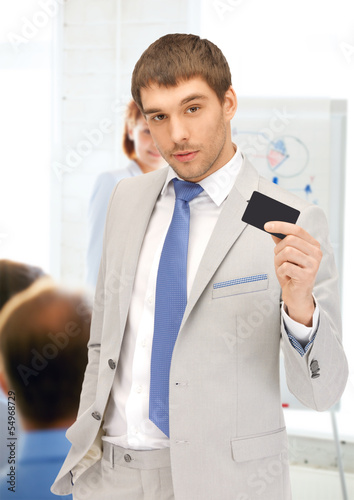 businessman showing credit card in office