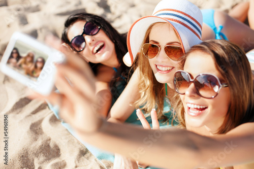 girls making self portrait on the beach