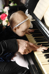 Cute baby sits at knees of her father and plays piano in room. F
