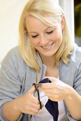 Frau schneidet Faden mit Schere