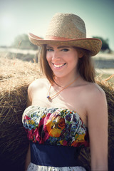 Portrait of young beautiful woman in the hayfield