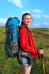 Hiking young woman with backpack and trekking poles outdoors