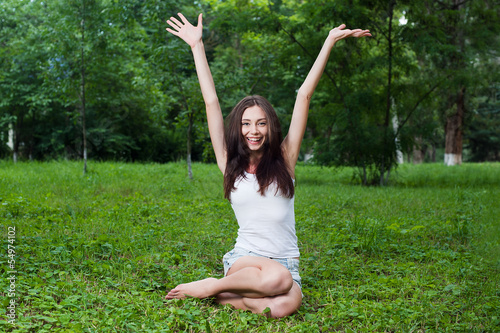 Happy young woman sitting on green grass with raised hands
