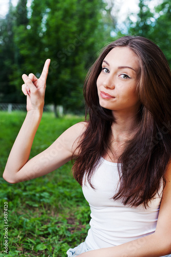 Smiling young woman pointing with her finger