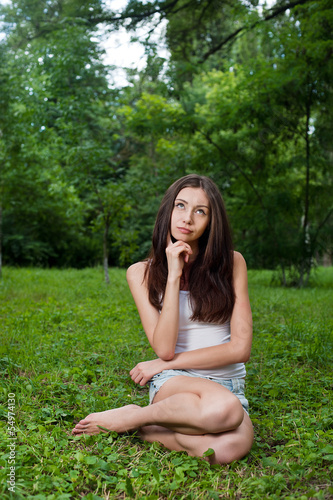 Thoughtful young woman outside in park