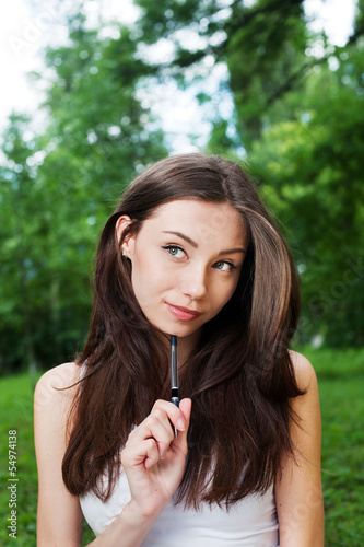 Thoughtful young woman with pen outside in park
