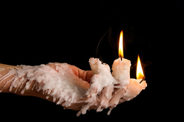 Three candle sticks on fingers buring