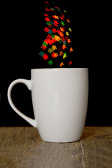 Bokeh heart spots of lights on background cup on wood