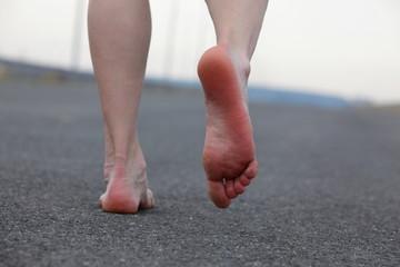 Closeup of man's bare feet walking away on the road