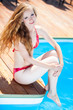 beautiful young woman resting on the edge of swimming pool