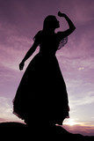 Silhouette of woman in flowing dress overlooking valley