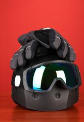 Winter sport glasses, helmet and gloves, on red background