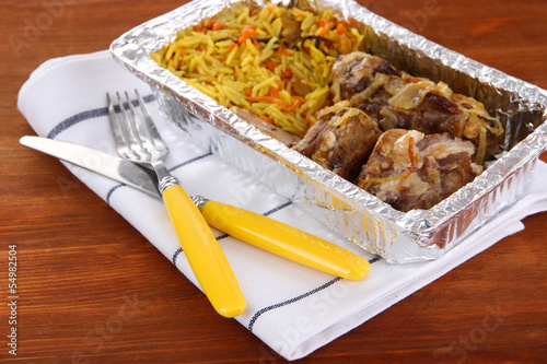 Food in box of foil on napkin on wooden background