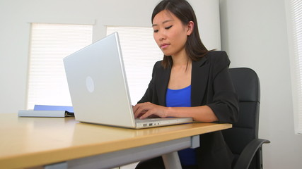 Hard working Chinese businesswoman typing at desk