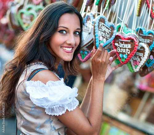 Young woman in Dirndl costume together with Gingerbread heart