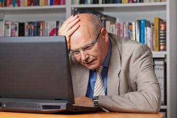 Enttäuschter und fassungsloser Senior vor Laptop