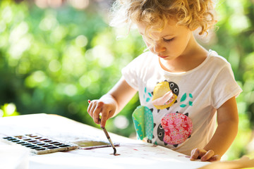 Portrait of little girl painting, summer outdoor