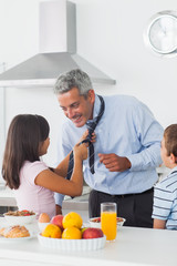 Daughter fixing her fathers tie with son in the kitchen