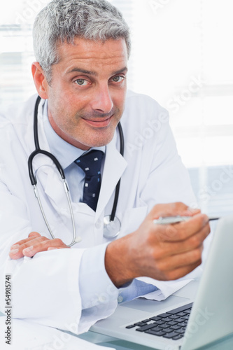 Smiling doctor watching something on his laptop