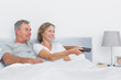 Smiling couple watching tv in bed