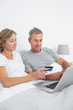 Cheerful couple using their laptop to buy online