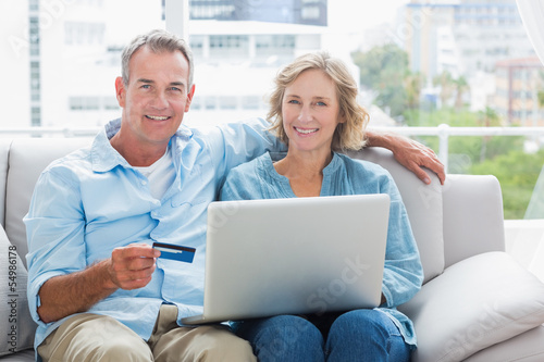 Happy couple sitting on their couch using the laptop to buy onli