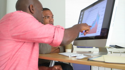 Two African American Business men looking at data on computer