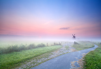 way to windmill in morning fog