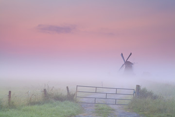 Dutch windmill in dense fog at sunrise