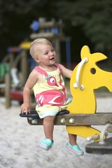 Happy adorable child swinging on a spring horse