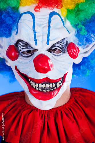 Scary clown person in clown mask on blue background