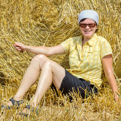 Organic farmer sitting in front of bales of straw