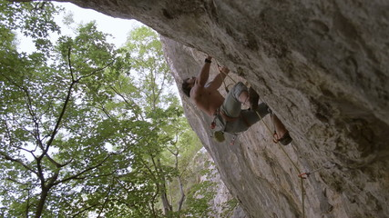 rock climber jumps for handhold
