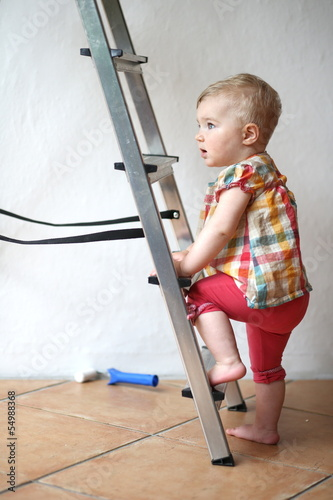 Cute little girl climbing on a step ladder