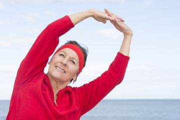 Mature woman stretching exercise ocean