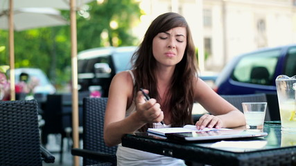 Angry, overwhelmed female student sitting in cafe
