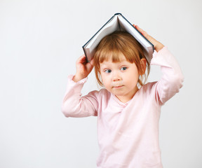 Cute little girl holding book on head