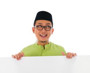 malay male with blank card during hari raya Eid al-Fitr celebrat