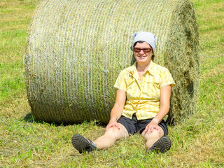 Farmer sitting in front of hay bales