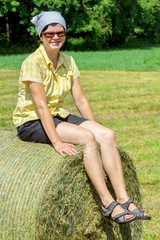 Peasant woman sitting on the hay bale