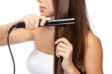 Young woman iwth a hair straightener