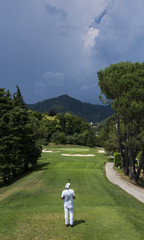 male golfer waiting to tee off under a cloudy sky