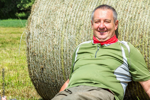 Organic farmer is resting against the hay bales