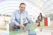 Deutschland, Leipzig, Geschäftsmann mit Laptop mit Geschäftsleuten im Hintergrund