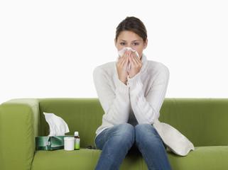 Junge Frau auf Sofa putzt sich die Nase
