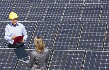 Deutschland, München, Ingenieure mit Laptop diskutieren an Solaranlage