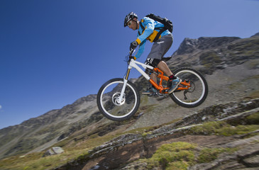 Frankreich, Dauphiné, Vaujany, Mountainbiker springend von Felsen
