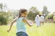 Deutschland, Bayern, Mädchen laufen mit Familie im Hintergrund