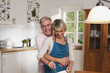 Deutschland, Kratzeburg, erwachsener Mann umarmt erwachsene Frau beim Kochen