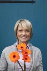 Deutschland, Kratzeburg, erwachsene Frau mit Blumenstrauß
